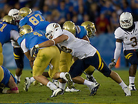 Dan Camporeale of California tackles UCLA quarterback Kevin Prince during the game at Rose Bowl in Pasadena, California on October 29th, 2011.  UCLA defeated California, 31-14.