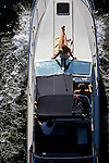 Opening Day of boating along the Montlake Cut with woman sunny herself on deck of yacht Seattle Washington State USA.