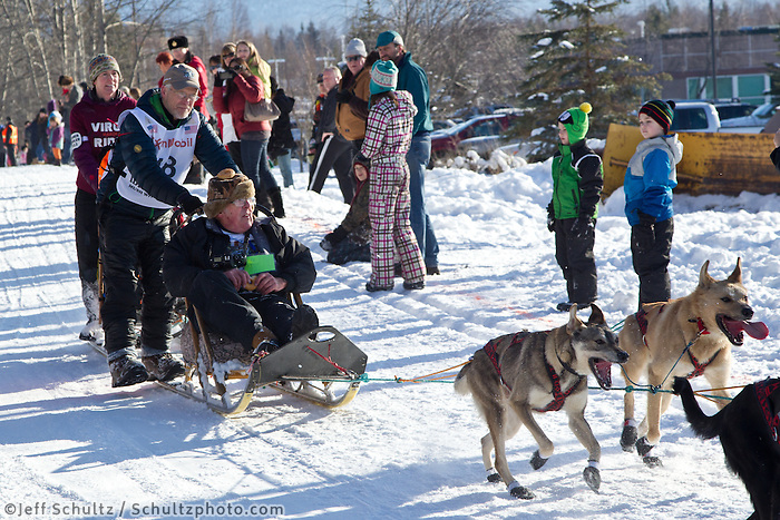 Jeff King and team run past spectators on the bike/ski trail during the Anchorage ceremonial start during the 2013 Iditarod race.    Photo by Britt Coon/IditarodPhotos.com