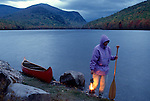 Woman on the shore of Lower South Branch Pond at twilight with lantern, Baxter State Park, Maine, USA, Piscataquis County