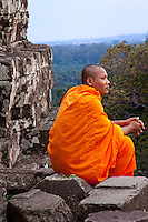 A buddhist monk atop ancient temple ruins pauses at sunset for a moment of reflection