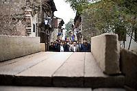 Turisti a passeggio nei vicoli di Wuzhen.<br /> Wuzhen &egrave; una piccola citt&agrave; della provincia dello Zhejiang chiamata anche la Venezia d'Oriente per la caratteristica dei canali che corrono lungo i vicoli dell'antica citt&agrave;. E' anche riconosciuta come uno dei centri pi&ugrave; importanti per la produzione e la lavorazione della seta nell'antichit&agrave;. Ancora sono presenti alcune piccole ditte che continuano a lavorare la seta con gli stessi metodi di come si faceva da secoli. Nonostante sia diventata una meta turistica ancora si pu&ograve; respirare la vecchia Cina passeggiando tra i vecchi vicoli costruiti con la pietra e rimasti intatti nei secoli.