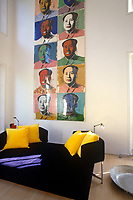 A series of screenprints of Chairman Mao by Andy Warhol arranged vertically down a long wall of the large double-height living space of a Richard Rogers house in London