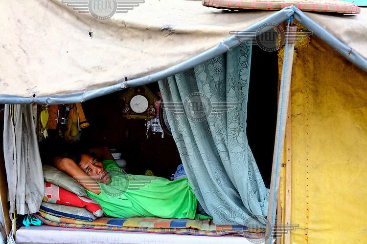 A man looks out from within his makeshift dwelling, typical of the housing occupied by many migrants who have moved to the city to work in its booming construction sector.