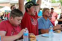 """MEGAN DAVIS/MCDONALD COUNTY PRESS Sean Lewis celebrates his win after eating six donuts in 1 minute and 27 seconds. Each competitor had a different strategy. Lewis took on the """"Big Mac"""" strategy, compressing and eating three donuts at a time."""