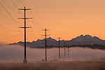 Large transmission towers with power lines in valley with early morning fog