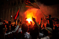 People have lit a fire and wave flags as they celebrate at Martyrs' Square in Tripoli. After a six month revolution, rebel forces finally managed to break into Tripoli and have taken control of Bab al-Aziziyah, Col Gaddafi's compound and residence. Few remain that are loyal to Gaddafi in the city; it is seeming that the 42 year regime has come to an end. Gaddafi is currently on the run.