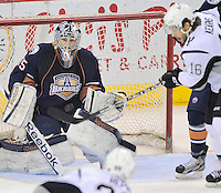Oklahoma City Barons goaltender Yann Danis, left, watches a shot as San Antonio Rampage's Bracken Kearns attempts to deflect the puck during the first period of an AHL hockey game, Thursday, May 10, 2012, in San Antonio. (Darren Abate/pressphotointl.com)