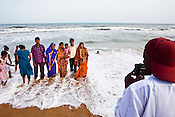A hired photographer (right) takes a photo of a family as they pose on Puri Beach along the Bay of Bengal in Puri, Orissa, India. A dip in its salty waters is believed to hold great religious significance, as a result these golden sand beaches sees is a never-ending rush of pilgrims and tourists. Photo: Sanjit Das/Panos