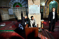 Watched over by a bodyguard, Iranian President Mahmoud Ahmadinejad votes at South Tehran's Bagherzadegan Mosque during elections for the Guardian Council..
