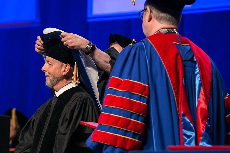 Craig W. Hartman, world-renowned architect, is hooded by Gerald P. Koocher, dean of the College of Science and Health, Sunday, June 11, 2017, during the DePaul University College of Science and Health and College of Liberal Arts and Social Sciences commencement ceremony at the Allstate Arena in Rosemont, IL. The Rev. Dennis H. Holtschneider, C.M., president of DePaul University looks on. (DePaul University/Jamie Moncrief)