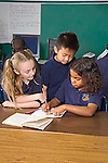 One Vietnamese American boy, one Caucasian blonde girl watch one mixed race girl in second grade write in notebook at desk in classroom in New Orleans
