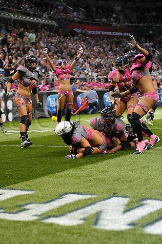 09.06.2012. Sydney, Australia.  Western Conference and Los Angeles Temptation quarterback Ashley Salerno scores a touchdown underneath Eastern Conference defenders while teammates celebrate in the Sydney LFL Australia All-Star Fantasy Game at Allphones Arena, Sydney Australia.