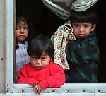 MARYDEL, MD, MARCH 23, 1999--Three young Guatemalan children play inside a windowless mobile home at Wilson's Trailer Park in rural Delaware.  These young immigrants, moved by thier families from Guatemala to Delaware so thier parents could forge a better life in the chicken processing plants that dot the Del Marva pennisula, make the best of their surroundings to play a child's game of peek-a-boo.  The photo speaks to childhood innocence in the face of an uncertain future.