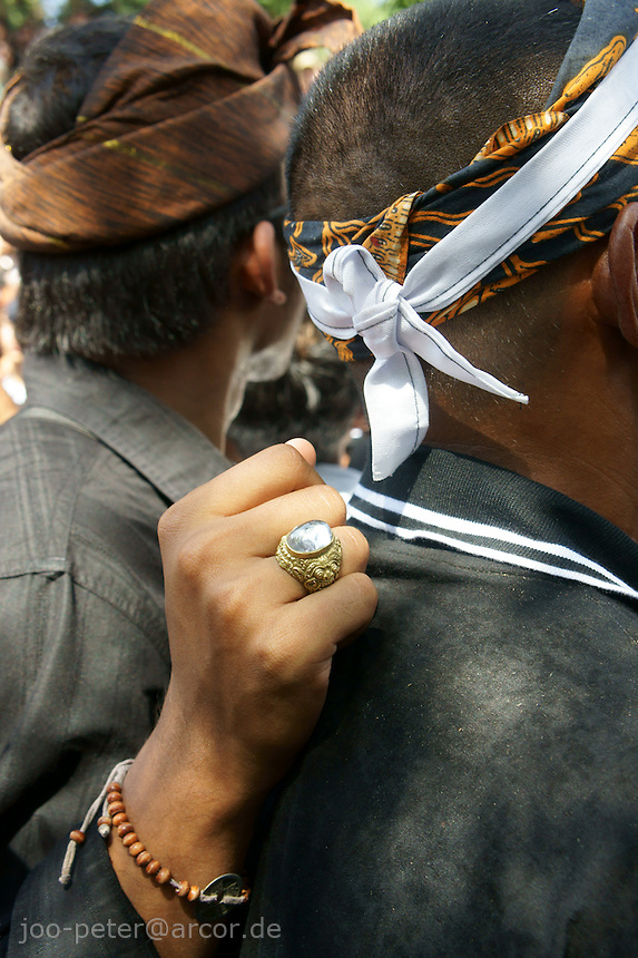 close-up of two Balinese watchting ceremonies for a cremation of a royal family member, August 2011, Ubud, Bali, archipelago Indonesia. One of the man is carryinga ring, which is believed to have magic power.
