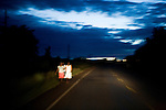 Woman walking along road at night, Uganda