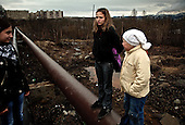 Girls stand on hot-water pipes in Zapolyarny, a nickel-processing sister town of Nikel. Sulphur dioxide from the factory kills vegetation, pollutes ground water and causes asthma.
