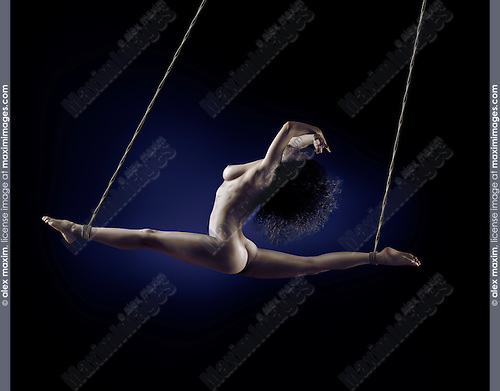Surreal artistic nude photo of a beautiful nude woman suspended in a front split with bondage ropes tied by her ankles on blue black background