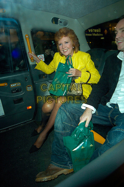 CILLA BLACK.At Pattie Boyd's Book Launch Party, Century Club,.London, England, August 28th 2007..full length bright neon yellow jacket slogan black t-shirt top skirt green bag sitting in car taxi cab.CAP/CAN.©Can Nguyen/Capital Pictures