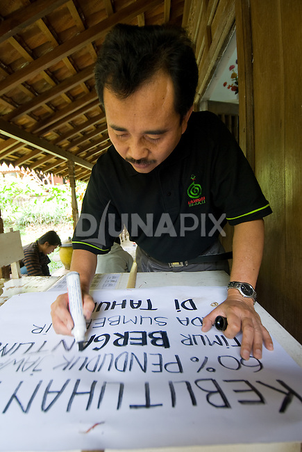 "Pak Masud of Kaliandra Sejati prepares a sign for the Dayurejo conservation carnival. The sign reads: ""The needs of 60% of East Java's population are dependent upon the water resources of community forest"""