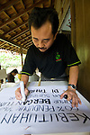 """Pak Masud of Kaliandra Sejati prepares a sign for the Dayurejo conservation carnival. The sign reads: """"The needs of 60% of East Java's population are dependent upon the water resources of community forest"""""""