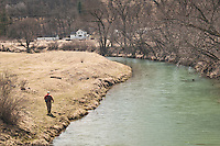 An angler walks along the Green River a trout stream in the Driftless Area of southwestern Wisconsin.