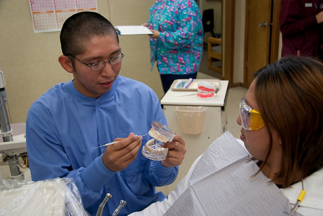A Native American dentist explains proper dental care and hygene to a patient at his clinic
