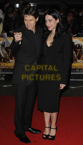 Willem Dafoe & Giada Colagrande .UK Premiere of 'John Carter' at BFI Southbank, London, England..March 1st 2012.full length suit blazer dress married husband wife black hand finger pointing .CAP/CAN.©Can Nguyen/Capital Pictures.