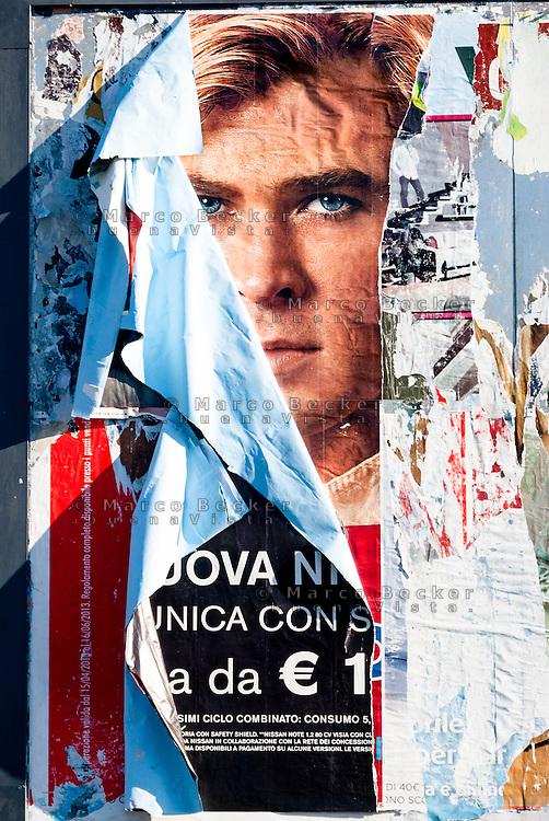 Milano, un volto sbuca da sotto ai manifesti strappati di un cartellone pubblicitario --- Milan, a face comes out from beneath the torn posters on a billboard