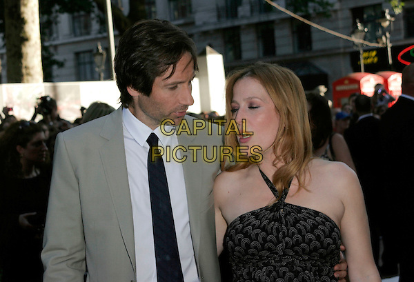 """DAVID DUCHOVNY & GILLIAN ANDERSON .Arrivals - """"The X-Files: I Want to Believe"""".UK  film premiere held at Empire Cinema, Leicester Square, London, England, 30th July 2008..X files half length  pregnant dress black print halterneck tie white shirt beige grey suit jacket eye shut funny mouth open.CAP/AH.©Adam Houghton/Capital Pictures"""