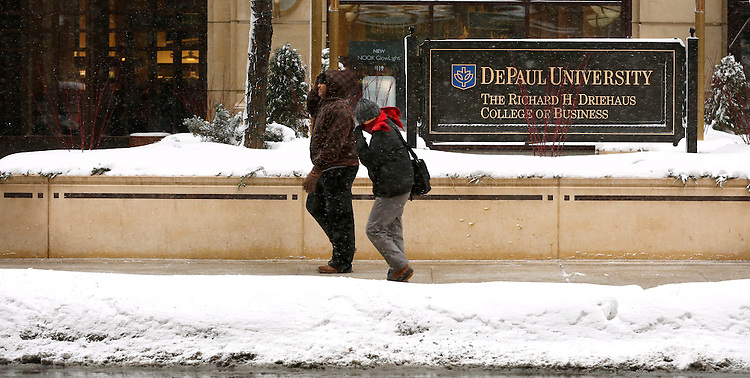 Pedestrians make their way past the Richard H. Driehaus College of Business as snow falls on the Loop campus of DePaul University in Chicago Thursday, Jan. 2, 2014. The New Year brought two days of lake effect snows to the downtown campus.  (Photo by Jamie Moncrief)