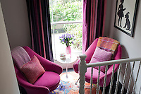 The half-landing has been turned into a cosy reading area with two pink armchairs and a rug by Nathalie Lete