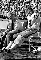 Oakland Raider quaterback Ken Stabler sitting injured on the bench with team doctor..(photo/Ron Riesterer)