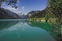 Reflection of mountain and trees, Lake Plansee near Reutte, Austrian Alps.