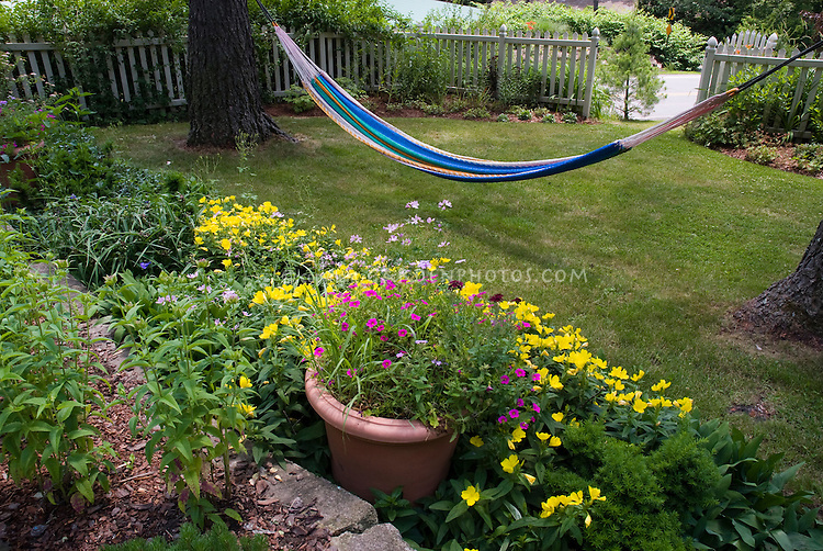 Hammock in shady lawn garden with container pot of flowers