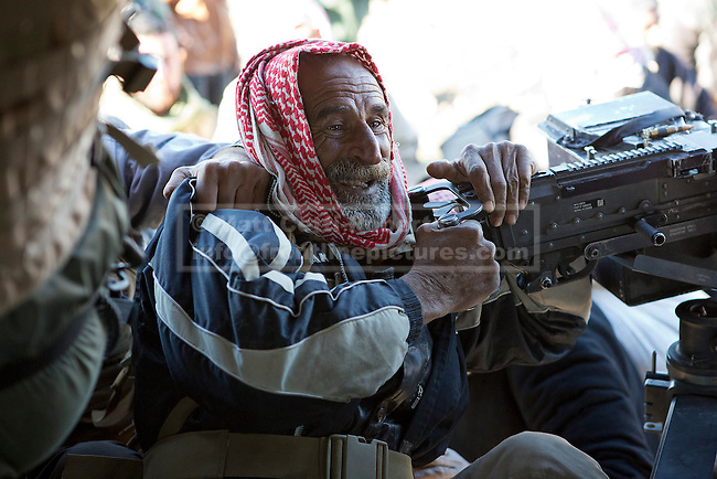11/12/2014. Sinjar Mountains, Iraq. An elderly Yazidi refugee hangs from an M240 machine gun as he attempts to climb in to an Iraqi Air Force Mi-171E helicopter, that will evacuate both he and his family from Mount Sinjar.<br /> <br /> Although a well publicised exodus of Yazidi refugees took place from Mount Sinjar in August 2014 many still remain on top of the 75 km long ridge-line, with estimates varying from 2000-8000 people, after a corridor kept open by Syrian-Kurdish YPG fighters collapsed during an Islamic State offensive. The mountain is now surrounded on all sides with winter closing in, the only chance of escape or supply being by Iraqi Air Force helicopters.