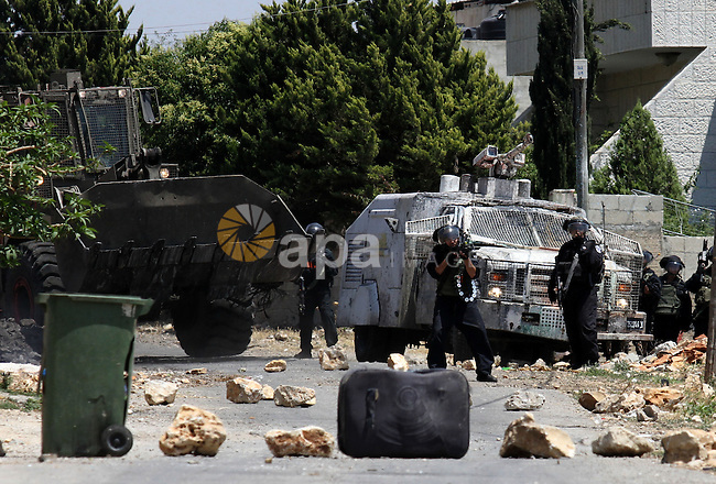 Israeli security forces stand guard next to their armoured vehicle during clashes with Palestinians following a demonstration against the expropriation of Palestinian land by Israel, on May 20, 2016 in the village of Kfar Qaddum, near Nablus, in the occupied West Bank. Photo by Nedal Eshtayah