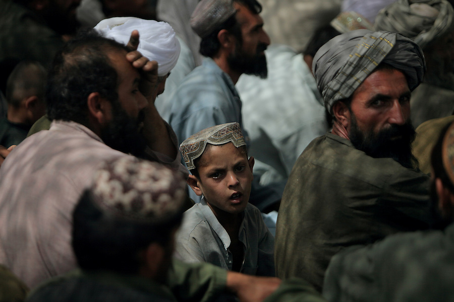 Hundreds of Afghan men attend a shura (or community meeting) on the grounds of a mosque in the Nawa District of Afghanistan's Helmand Province on July 23, 2009. The shura was led by the provincial governor Gulab Mangal, local Afghan National Army and National Police commanders, and US Marine Brigadier General Lawrence D. Nicholson.