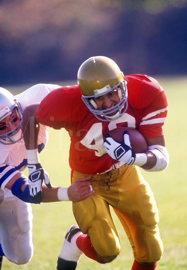 Running back trying to elude a tackler.