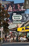 Sidewalk cafes and giant billboards at the Sunset Plaza area of the Sunset Strip in Los Angeles, CA