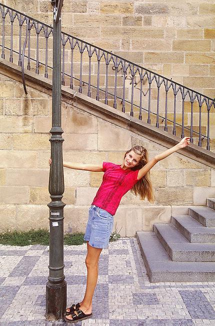 Une femme au pied d'un escalier *** A woman in front of a staircase.