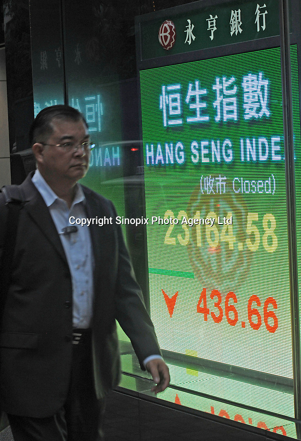 A passerby walks by  Wing Hang Bank where a large-size electronic screen indicates the Hang Seng Index(HSI), Hong Kong SAR, China. The Hang Seng Index is a free float-adjusted market capitalization-weighted stock market index in Hong Kong. It is used to record and monitor daily changes of the largest companies of the Hong Kong stock market and is the main indicator of the overall market performance in Hong Kong..