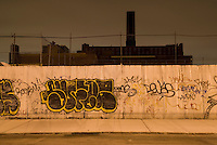 Williamsburg, Brooklyn, New York City, New York State, USA....Cityscape at Night, Street, Sidewalk, Metal Wall with Graffiti, Landmarked Domino Sugar Refinery (built in 1884) in the distance.