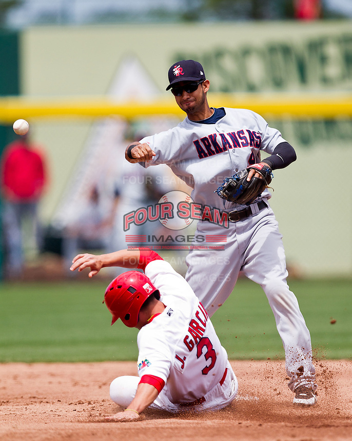 Renny Osuna (9) of the Arkansas Travelers turns a double play during a game against the Springfield Cardinals at Hammons Field on May 8, 2012 in Springfield, Missouri. (David Welker/ Four Seam Images).