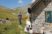 Bernard Bruno picks up mobile phone reception at the shepherd's cabin where he lives during 3 summer months while his sheep graze the mountain pastures around the Plateau de Longon, Mercantour National Park, French Alps, France, 01 August 2013.