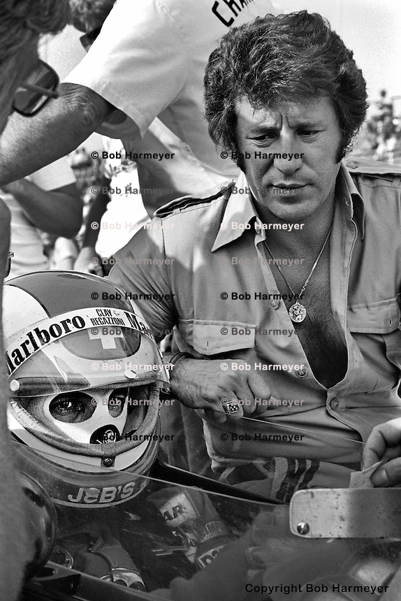 INDIANAPOLIS, IN: Clay Regazzoni prepares to drive his  McLaren M16C 4/Offenhauser TC while Mario Andretti waits to offer advice before practice for the Indianapolis 500 on May 29, 1977, at the Indianapolis Motor Speedway.