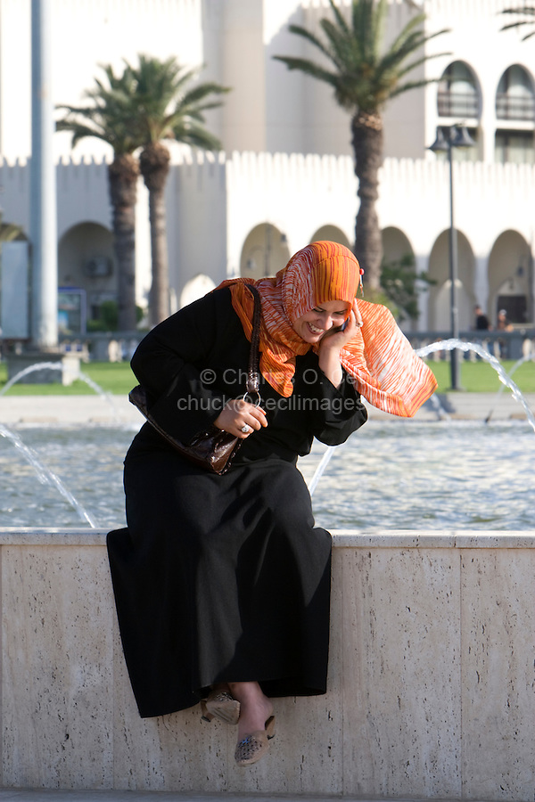 Tripoli, Libya, North Africa - Modern Libyan Women's Clothing Style as seen in Public Park near the Green Square, downtown Tripoli.  Talking on Cell Phone.