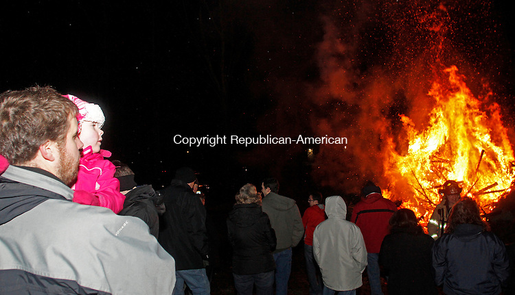 Woodbury, CT011814MK01 Josh Meeker holds his four year old daughter Madeline  as they watch trees burn during the Woodbury Volunteer Fire Department's annual Twelfth Night Christmas Tree Burn in Woodbury on Saturday evening.  Fire chief Morgan said that 300 trees had been collected for the burn which has been held annually for nearly twenty-five years.  Michael Kabelka Republican-American