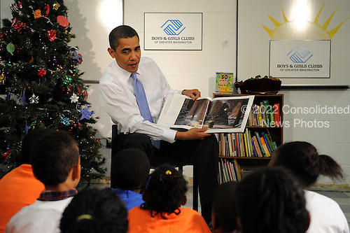 "Washington, DC - December 21, 2009 -- United States President Barack Obama reads ""The Polar Express"" to elementary aged children at a Boys and Girls Club in Washington on Monday, December 21, 2009. After reading the President passed out cookies. .Credit: Roger L. Wollenberg / Pool via CNP"