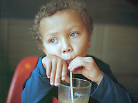 A portrait of a young boy drinking juice